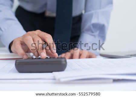 Close up of businessman hand working on accountancy document, calculator and laptop computer, e business concept