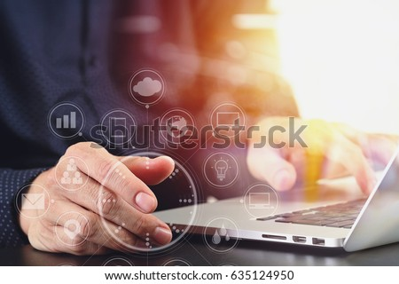 close up of businessman hand working with laptop computer in modern office with virtual icon diagram