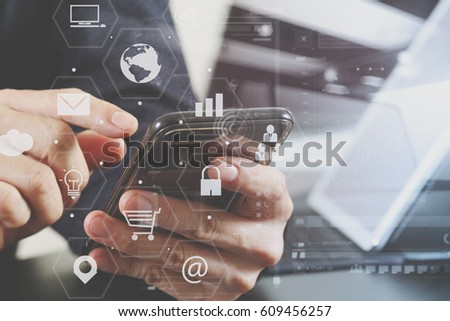 close up of businessman hand working with smart phone and laptop and digital tablet computer in modern office with virtual icon diagram