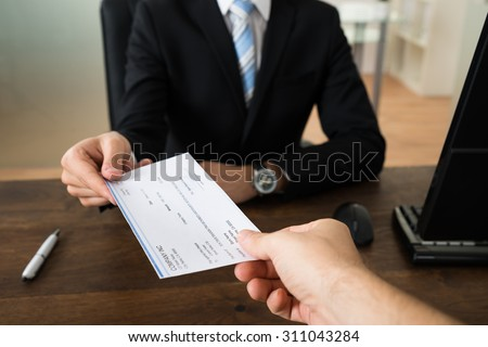 Close-up Of Businessman Hands Giving Cheque To Other Person In Office #311043284