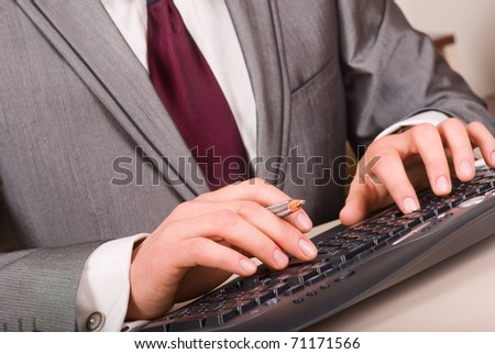 Close-up of businessman hands with pen typing on black computer keyboard