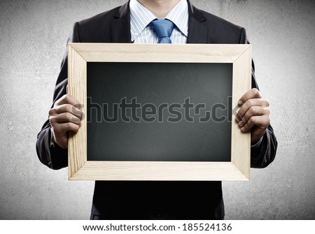 Close up of businessman holding blank frame. Place for text