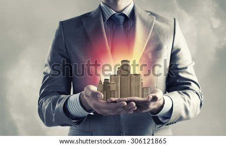 Close up of businessman holding city model in hands #306121865