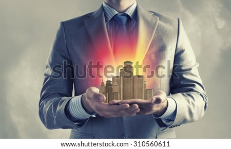 Close up of businessman holding city model in hands #310560611