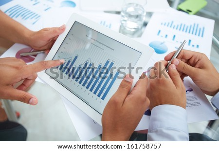 Close-up of businessman holding electronic document in touchpad and pointing at it during discussion