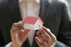 Close up of businessman holding model house. Architecture, building, construction, real estate and property concept