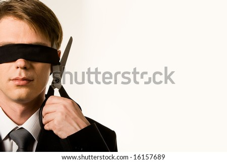 Close-up of businessman holding scissors while cutting black band on his eyes