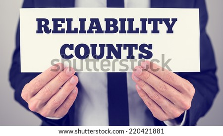 Close Up of Businessman Holding Sign Reading Reliability Counts.