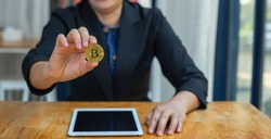 Close up of businessman holding some pieces of golden Bitcoin token over the tablet on wooden table. Bitcoin is one of the popular cryptocurrency, a virtual currency or a digital currency concept.