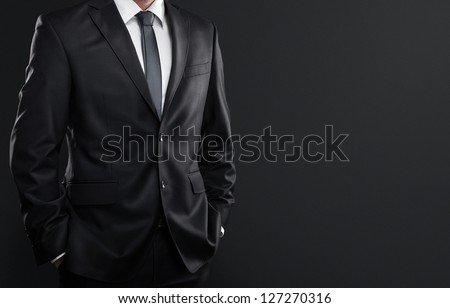 Close up of businessman in suit over dark gray background with copy space Stock photo ©