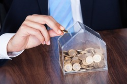 Close-up Of Businessman Inserting Euro Coin In Money Box
