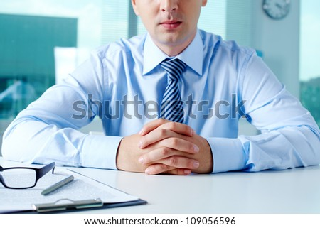 Close-up of businessman keeping fingers crossed in front of himself
