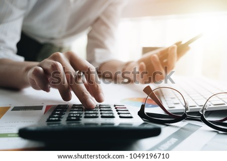Close up of businessman or accountant hand holding pen working on calculator to calculate business data, accountancy document and laptop computer at office, business concept #1049196710