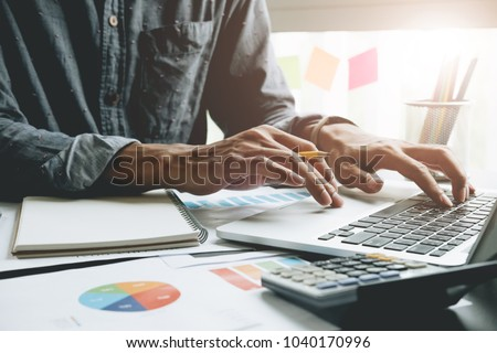 Close up of businessman or accountant hand holding pen working on laptop computer for calculate business data, accountancy document and calculator at office, business concept