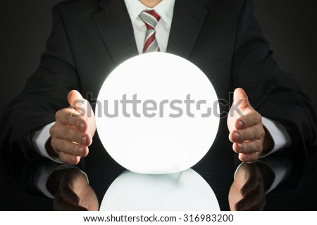 Close-up Of Businessman Predicting Future With Crystal Ball At Desk #316983200