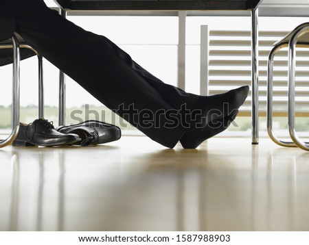 Close up of businessman�s feet with shoes off under table