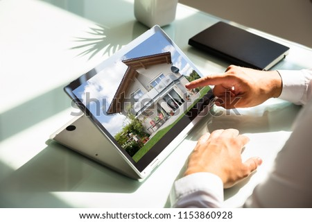Close-up of businessman's hand checking house on laptop