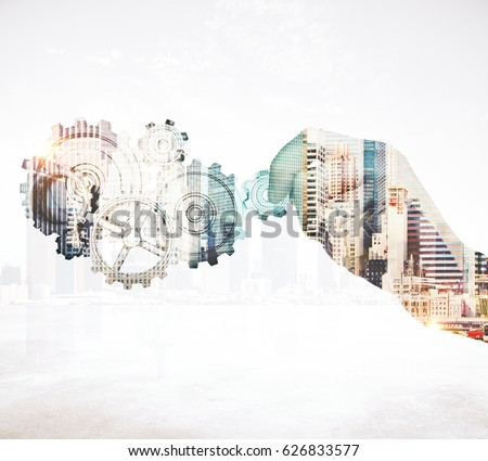 Close up of businessman's hand holding abstract cogs on city background. Teamwork concept. Double exposure