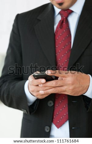 close up of businessman's hands holding cell phone