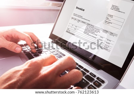 Close-up Of Businessman's Hands Working On Invoice On Laptop At Office