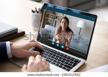 Close up of businessman talk with female business partner or client using video call on laptop, male employee talk consult with coach on webcam conference on computer, online consultation concept