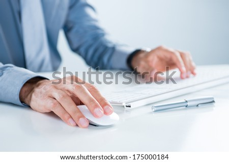 Close Up Of Businessman Using Computer At Desk In Office