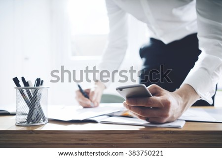Close up of businessman using smartphone and working on documents at office, success man employer in office interior with cellphone and contract on desk #383750221