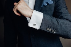 Close up of businessman wearing cufflinks. Elegant young fashion business man wearing suit.