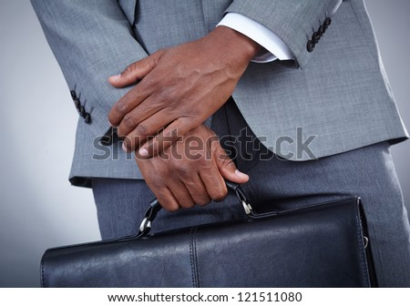 Close-up of businessman with briefcase in hand isolated on grey background