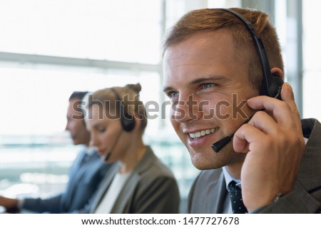 Close-up of Businessman with his colleagues talking on headset in office. Modern corporate start up new business concept with entrepreneur working hard