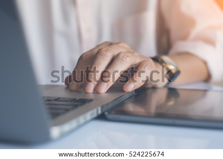 Close up of businessman working on laptop computer and tablet pc and rest his hand on keyboard with reflection, online working internet of things IOT, warm tone.