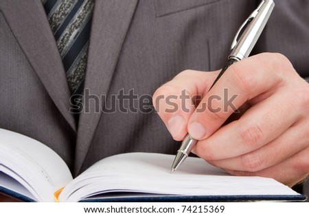 Close-up of businessman writing in business diary