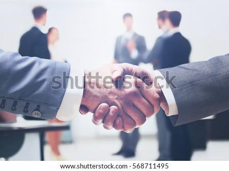 Close up of businessmen shaking hands - Shutterstock ID 568711495