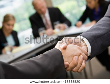 Close up of businessmen shaking hands in conference room - stock photo