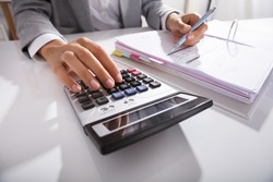 Close-up Of Businessperson Calculating Bills With Calculator In Office