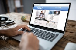 Close-up Of Businessperson Checking Online News On Laptop At Desk