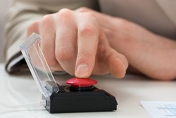 Close-up Of Businessperson Hand Pressing Red Emergency Button