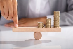 Close-up Of Businessperson's Finger Balancing Stacked Of Coins On Wooden Seesaw