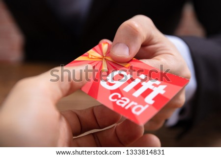 Close-up Of Businessperson's Hand Giving Red Gift Card To Other Businessperson