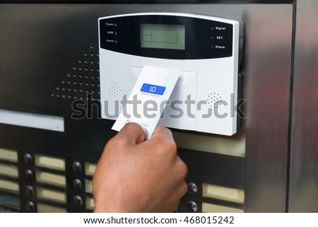 Close-up Of Businessperson's Hand Holding Keycard To Open Door