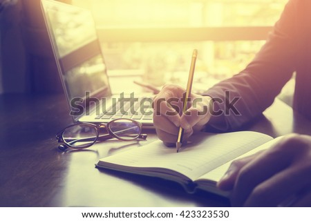 Close-up Of Businessperson Signing Contract,Man writing paper at the desk with pen and reading books at table with basic business Form document working in office ,morning light ,selective focus.