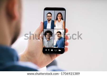 Close-up Of Businessperson Videochatting With Male Colleague On Mobile Phone