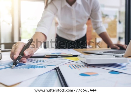 Close-up of businesswoman pointing and analysis business strategy for financial graph on clipboard with computer labtop on her wooden desk in office.