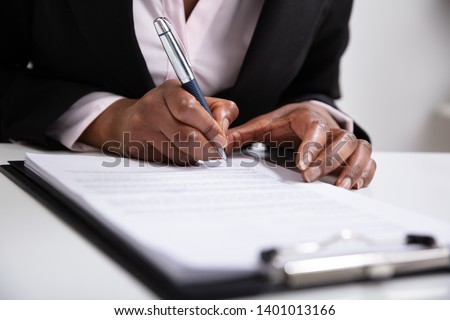 Close-up Of Businesswoman's Hand Signing On Papers Over Desk
