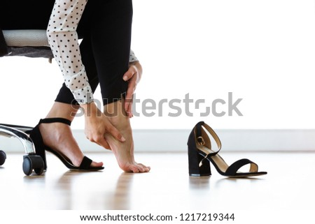 Close up of businesswoman sitting on a chair and massaging her hurting toes after wearing every day heels. #1217219344