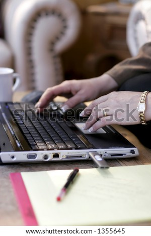 Close up of businesswoman working at laptop in a business travel hotel (shallow focus point on foreground hand).