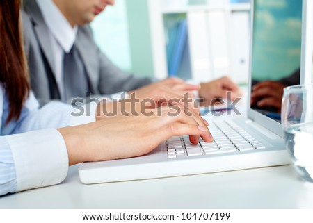 Close-up of businesswoman working with laptop at workplace