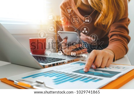 close up of businesswoman working with smart phone and laptop and digital tablet computer in modern office with virtual icon diagram