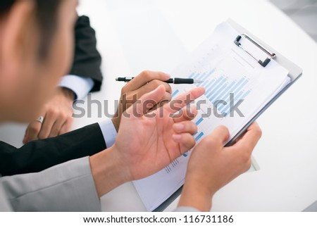 Close-up of busy businessmen analyzing financial results