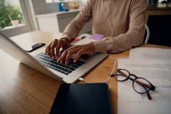 Close-up of busy female hand typing on keyboard while sitting at her home with documents and eyeglasses